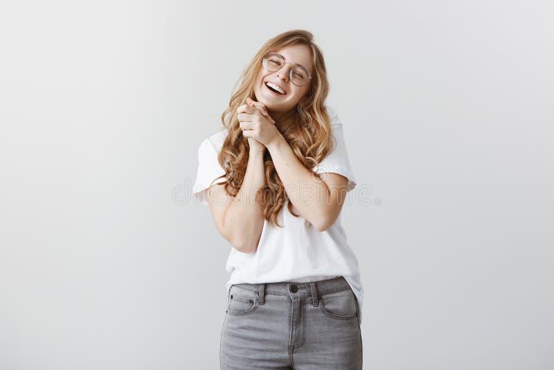 Oh, tan dulce Retrato de la chica joven encantadora contenta en los vidrios transparentes, sonriendo ampliamente, apretando las p fotos de archivo libres de regalías