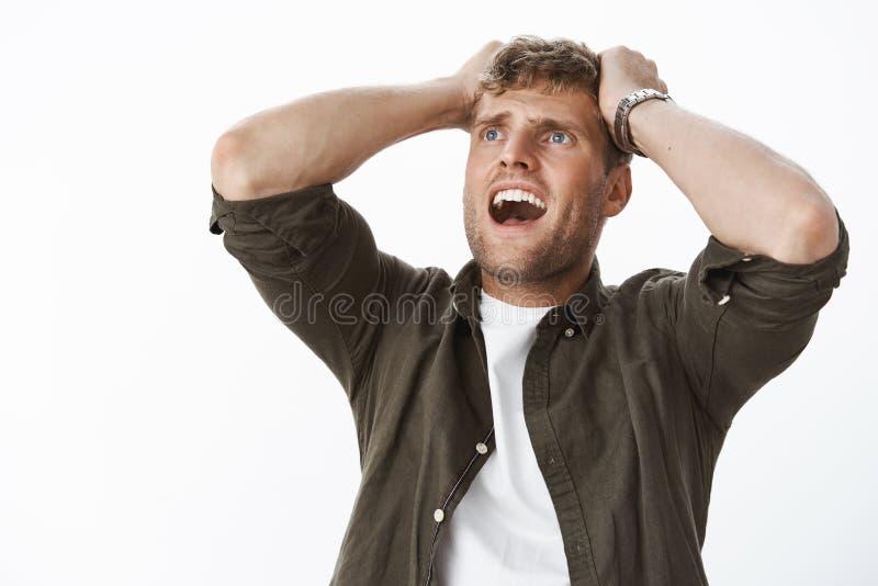 Oh un dieu ce qui font Homme blond bel soucieux tenant des mains sur le chef dans la panique hurlant la recherche être concerné e image stock