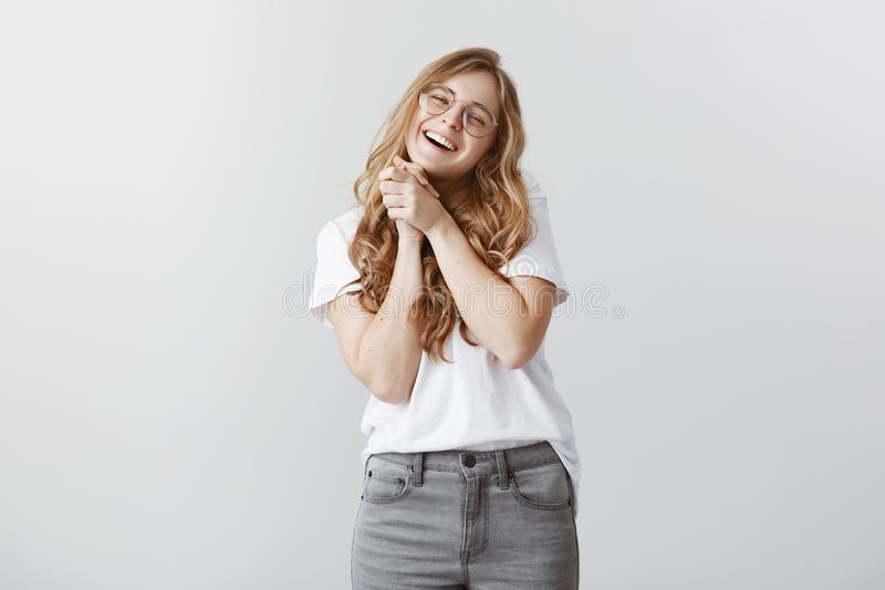 Oh, w ten sposób słodki Portret zadowolona powabna młoda dziewczyna w przejrzystych szkłach zaciska palmy wpólnie, ono uśmiecha s zdjęcia royalty free