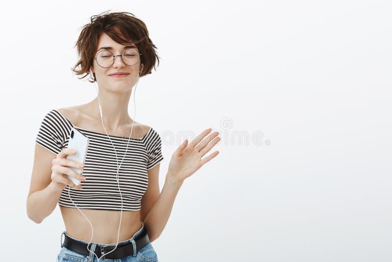 Oh yeah, ulubiona piosenka robi ja tanczyć Szczęśliwa zrelaksowana atrakcyjna dziewczyna z krótkim brązu włosy w szkłach i croppe zdjęcie royalty free