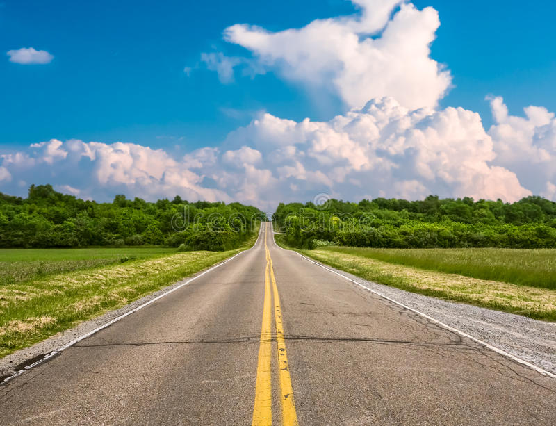 Ohio Country Road. An old country road rolls over hills and through a thick forest stock image