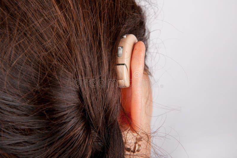 Ohr einer Frau mit Hörgerät von der Rückseite lizenzfreie stockbilder