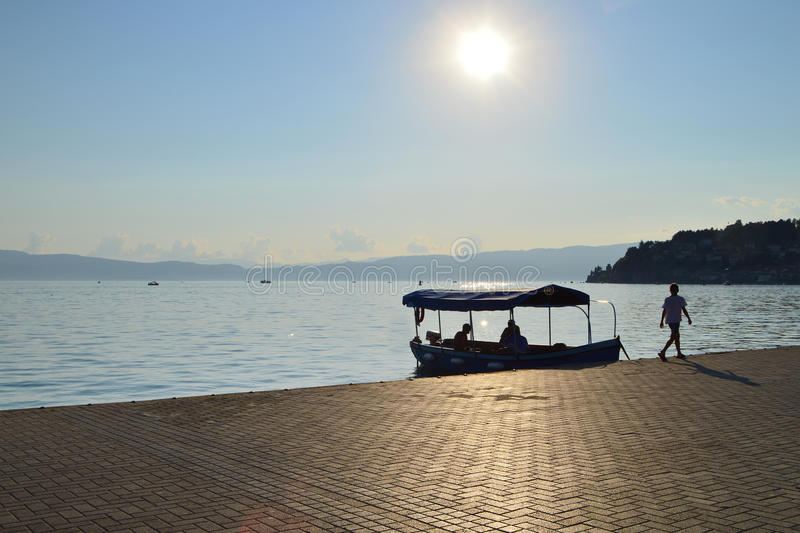 Ohrid Lake on sunset. Ohrid, Macedonia – August 28, 2015: Waiting for tourists old tourist boat on Ohrid Lake at sunset. Kid walking on the promenade of Ohrid stock images