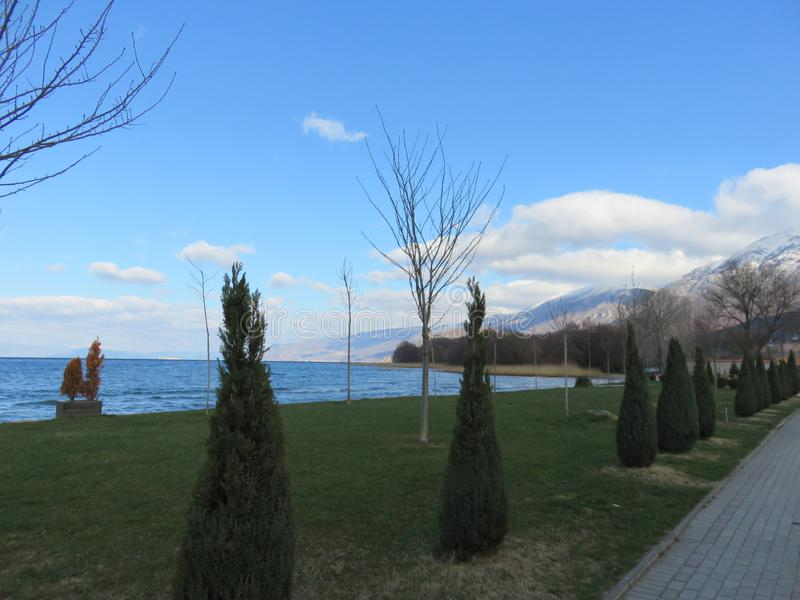 Ohrid lake and walking path next to it. Photo of Ohrid lake and walking path next to it, bright blue sky with white clouds in background royalty free stock photo