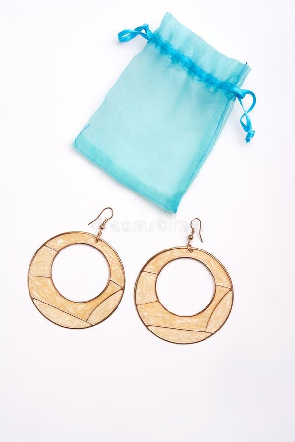 Ohrring und blauer Schmuck bauschen sich auf weißem Hintergrund stockfotografie