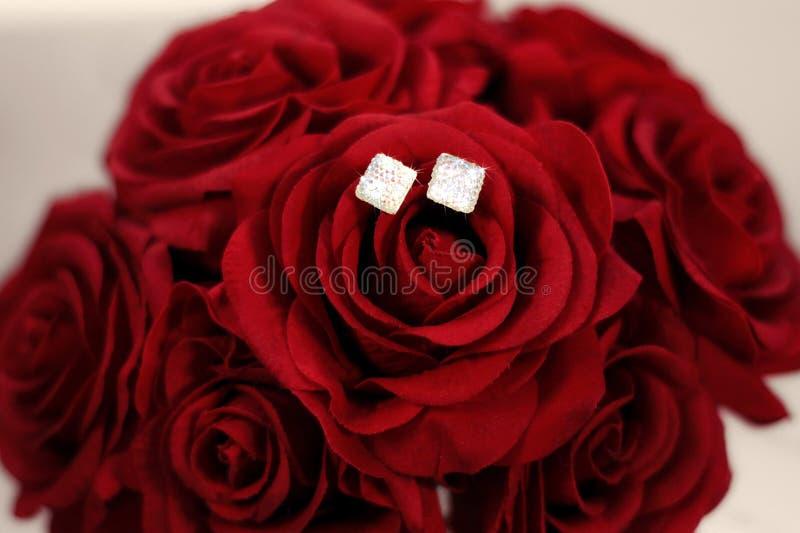 Ohrringe auf einem Blumenstrauß von Rosen lizenzfreie stockfotografie