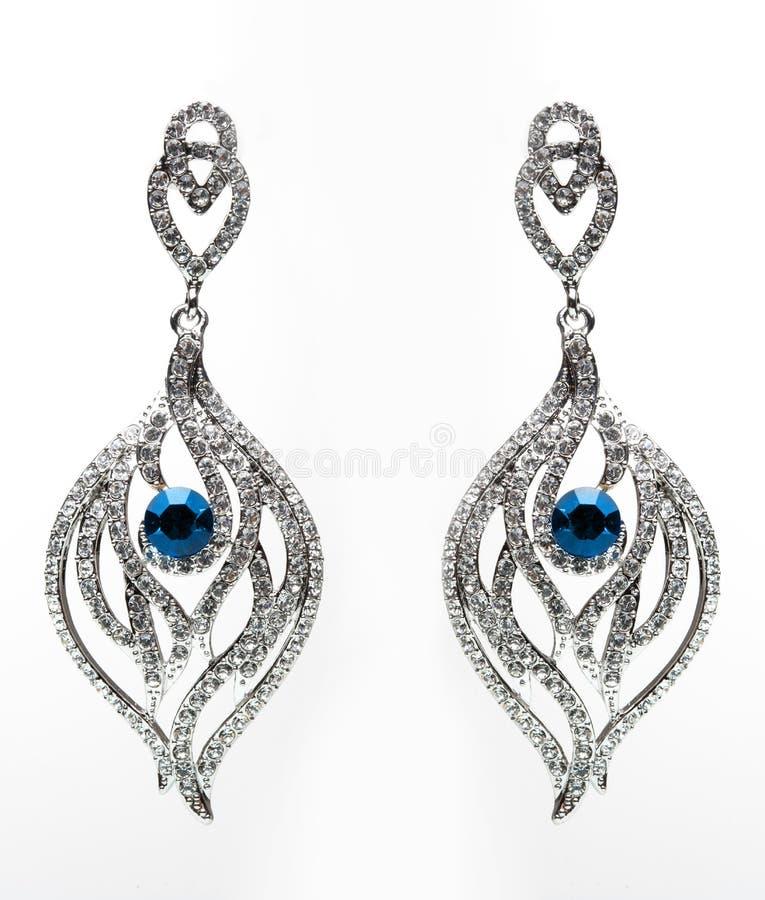 Ohrringe mit blauen Steinen auf dem Weiß lizenzfreie stockfotografie