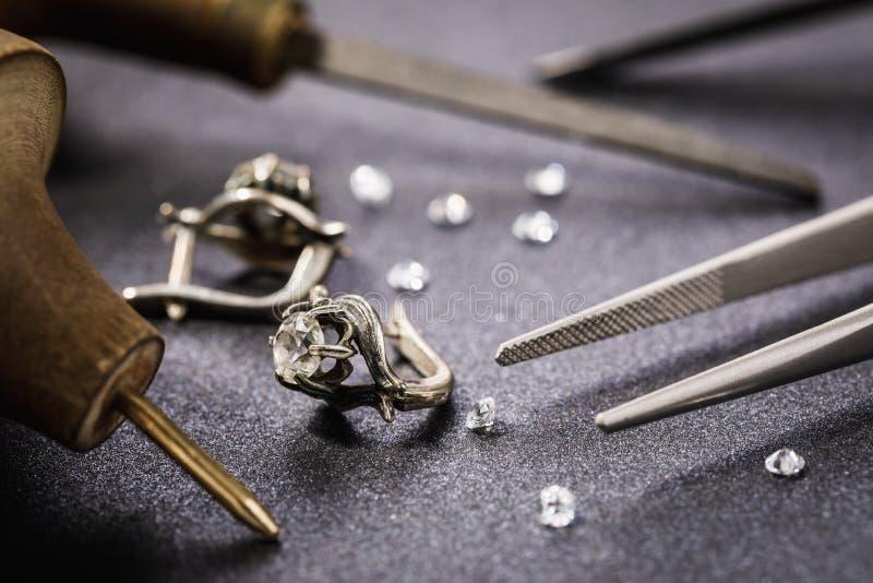 Ohrringe mit einem Stein auf dem Tisch, umgeben durch Werkzeuge für die Reparatur des Schmucks stockfoto