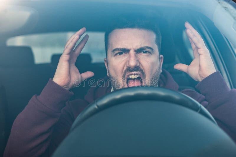 Ohyfsad man som kör hans bil och argumentera arkivfoton