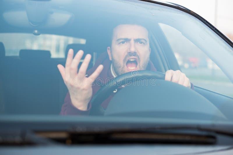 Ohyfsad man som kör hans bil och mycket argumenterar arkivfoto