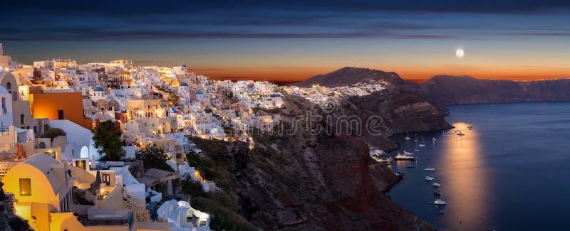 Oia村庄的全景在圣托里尼海岛上的有满月的 图库摄影