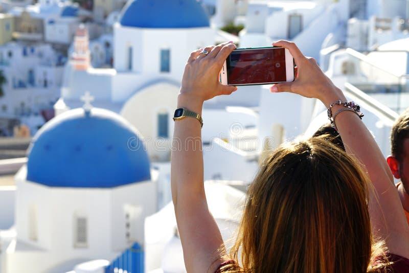 OIA GREKLAND, September 19, 2018 a-turisten tar ett fotografi genom att använda en telefon royaltyfri fotografi