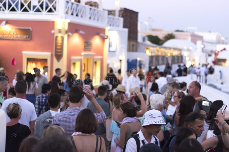 Oia Santorini, GREKLAND - Juni 9, 2017: EN FOLKMASSA AV TURISTER VÄNTAR PÅ DEN BERÖMDA SANTORINI-SOLNEDGÅNGEN arkivfoton
