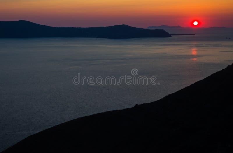 Oia santorini island greece. Natural coloured sunset. Dark red sky. Gold setting sun behind mountains. Calm sea reflecting stock image