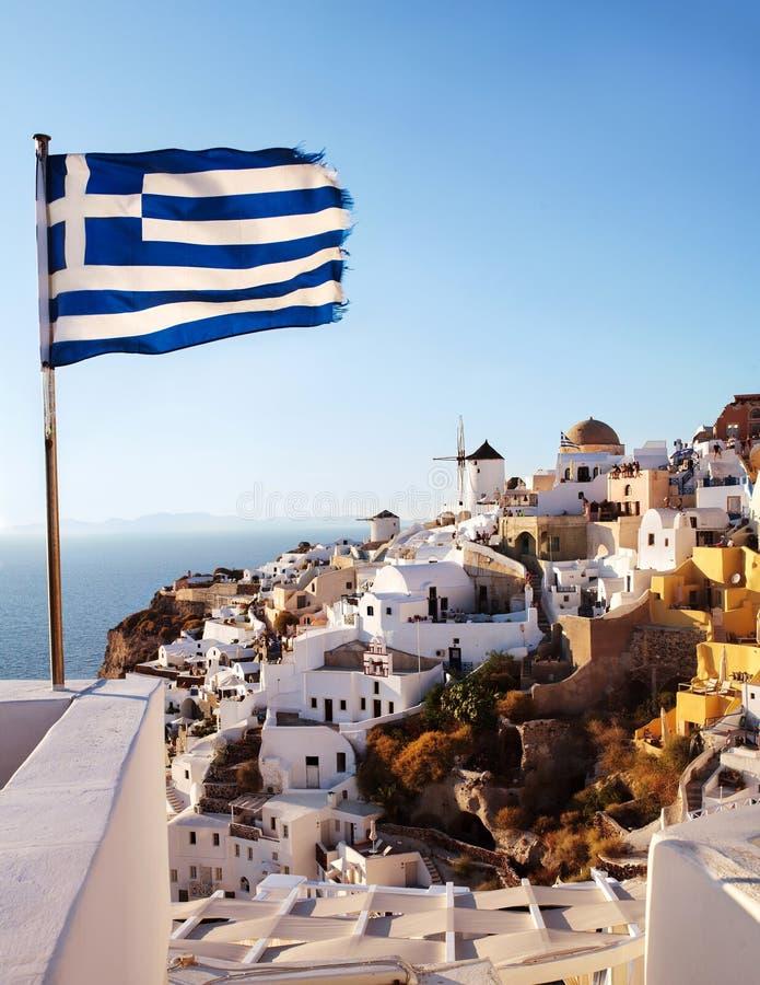 Oia, Santorini Windmolen aan klippenkant, en Griekse vlag royalty-vrije stock afbeelding
