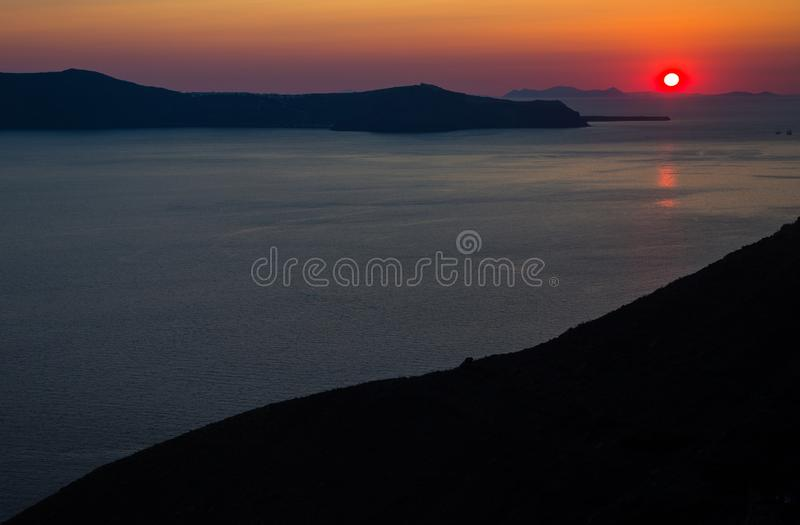 Oia santorinieiland Griekenland Natuurlijke gekleurde zonsondergang Donkerrode hemel Gouden het plaatsen zon achter bergen Het ka stock afbeelding