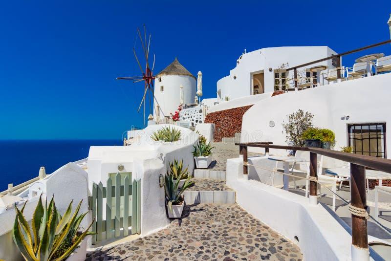 Oia stad, Santorini ö, Grekland Väderkvarnar på klippa, cobled s arkivbilder