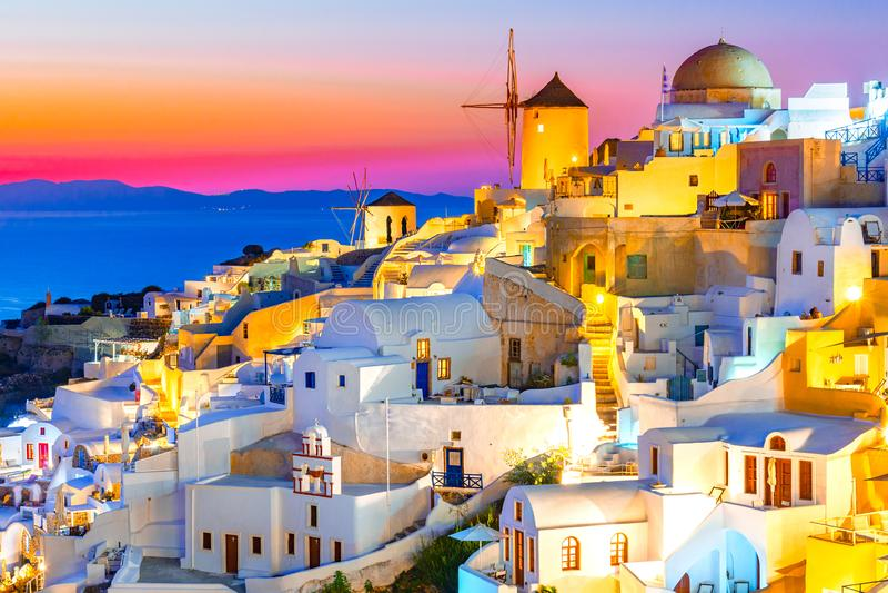 Oia stad, Santorini-eiland, Griekenland bij zonsondergang Traditionele en beroemde witte huizen en kerken met blauwe koepels over stock foto