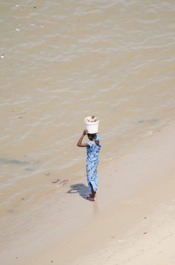 Oidentifierad afrikansk kvinna i blåttklänninganseende på stranden som balanserar hinken royaltyfri fotografi