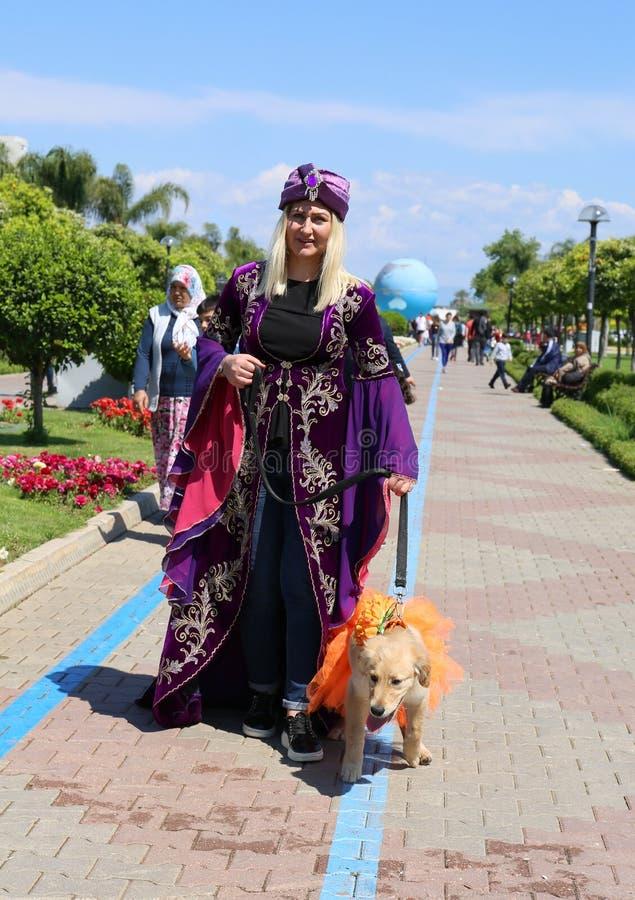 Oidentifierad blond kvinna med hunden som poserar på den orange blomningkarnevalet arkivfoton