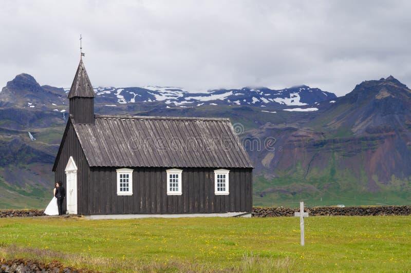 Oidentifierad brud och brudgum som framme står av berömd svart kyrka i Budir, Island royaltyfri fotografi