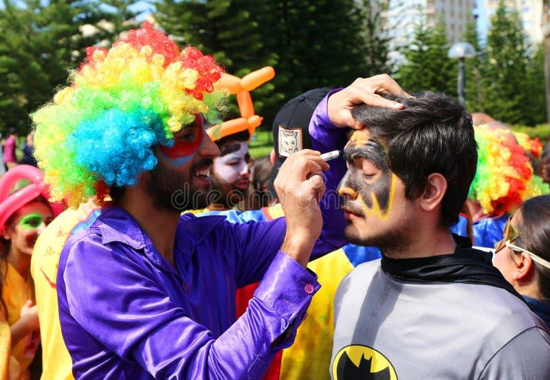 Oidentifierad clownmålninggrabb med framsidan för Batman dräkt` s på den orange blomningkarnevalet royaltyfria bilder