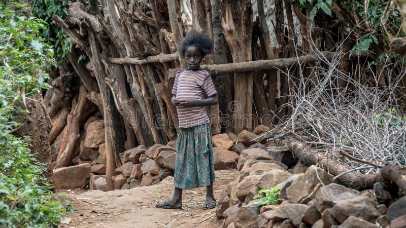 Oidentifierad etiopisk flicka som går i hennes by royaltyfria bilder