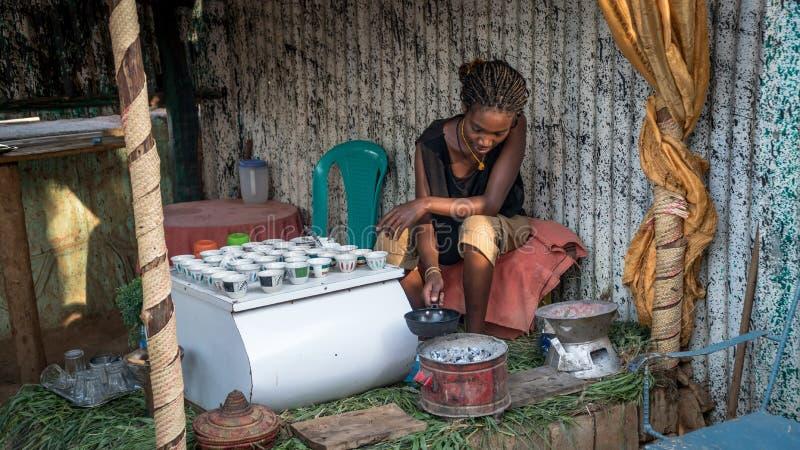 Oidentifierad etiopisk kvinna som gör traditionellt kaffe i en koja royaltyfria bilder