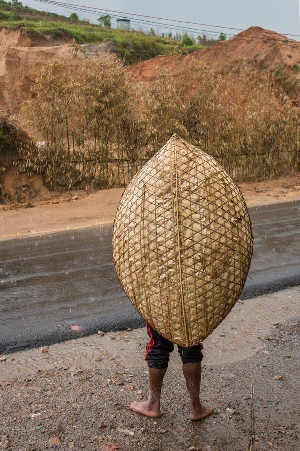 Oidentifierad khasiman som bär den traditionella regnräkningen som göras från bambu arkivfoto