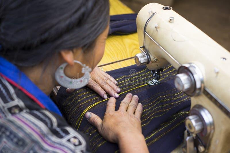 Oidentifierad kläder för danande för kvinna för H-`-mong vid den närliggande symaskinen hennes hus Hmongen är en asiatisk folkgru royaltyfri bild