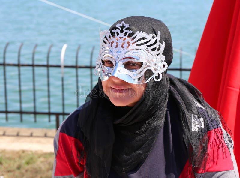 Oidentifierad kvinna med maskeringen och hijab som poserar på den orange blomningkarnevalet arkivbilder