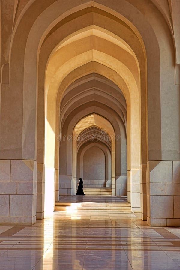 Oidentifierad kvinna som går under båge av sultan byggnadskomplex, i Muscat arkivfoton