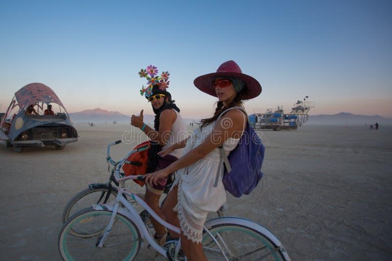Oidentifierad man och kvinna som rider en cykel royaltyfri bild