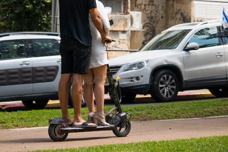 Oidentifierad man och kvinnor som rider en elektrisk sparkcykel royaltyfria bilder