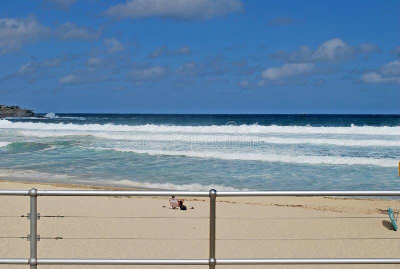 Oidentifierad person i en sunbed tyckande om sikt av vågorna på den tomma Bondi stranden i Sydney royaltyfri bild