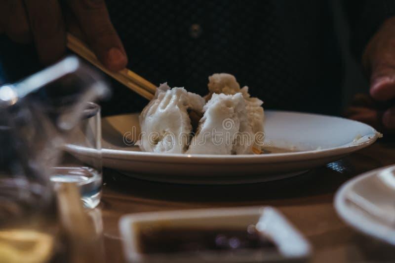 Oidentifierad person som äter rödingsiu-bao med pinnar royaltyfria bilder