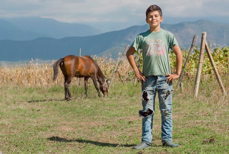 Oidentifierad pojke som har gyckel i lantgård av hans familj med hästen och vingård i den gröna dalen royaltyfri fotografi
