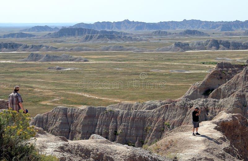 Oidentifierad turist som två tycker om sikten av Badlandsnationalparken i South Dakota royaltyfri bild