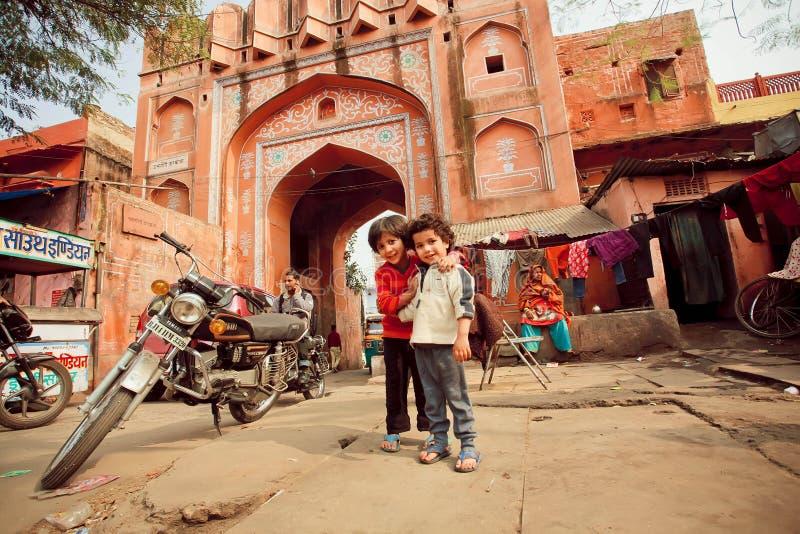 Oidentifierade barnvänner som har gyckel på fattigt folkområde med fullsatta gator fotografering för bildbyråer