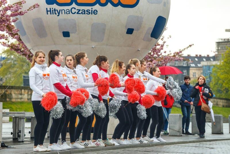Oidentifierade hejaklacksledare som stöttar löpare under maraton för 16 Cracovia royaltyfri fotografi