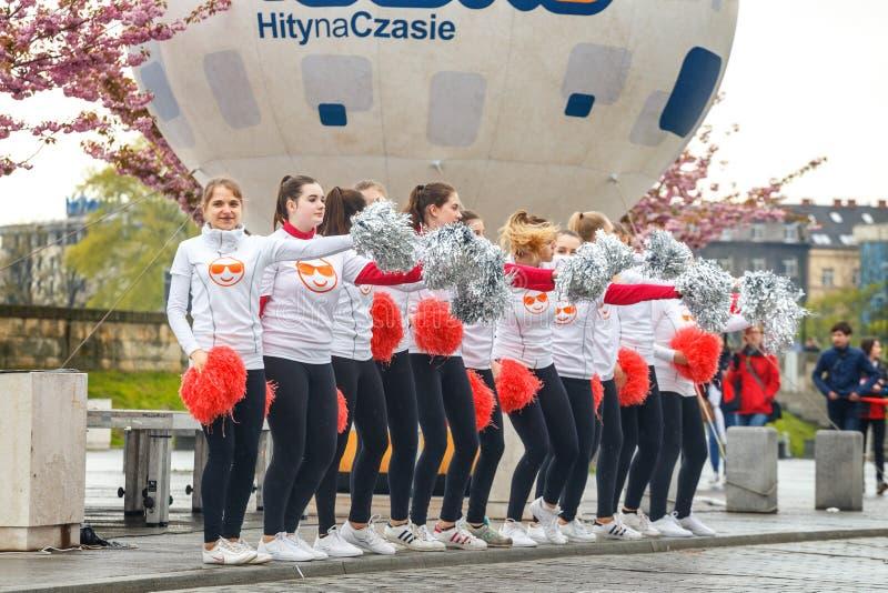 Oidentifierade hejaklacksledare som stöttar löpare under maraton för 16 Cracovia royaltyfri bild