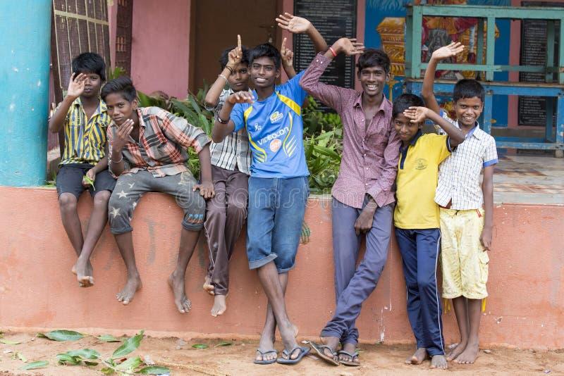 Oidentifierade lyckliga lantliga fattiga barntonåringar som spelar på gatan av byn arkivfoto