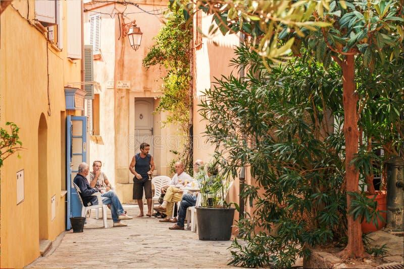 Oidentifierade män i den lilla gatan på Saint Tropez, Frankrike arkivfoto