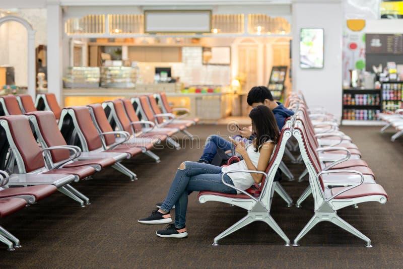 Oidentifierade par genom att använda mobiltelefonen, medan sitta på stol i vardagsrumzon arkivbild