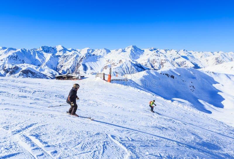 Oidentifierade skidåkare tycker om att skida på lutningen i fjällängarna arkivfoto