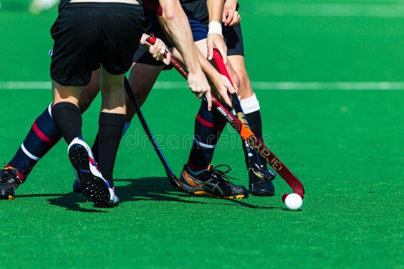 Oidentifierade spelare Clash Ball Sticks för hockey arkivbilder