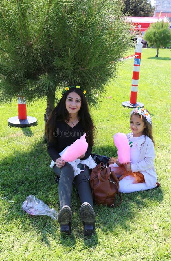 Oidentifierade systrar som sitter på gräs och tycker om deras sockervaddar royaltyfria foton