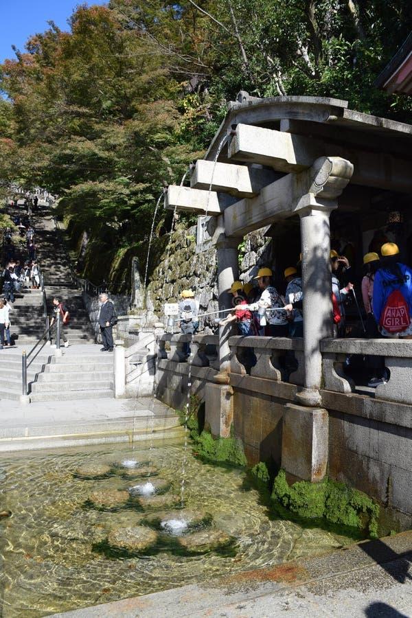 Oidentifierade turister som samlar vatten från deningen-taki vattenfallet på den Kiyomizu templet, Kyoto arkivbild