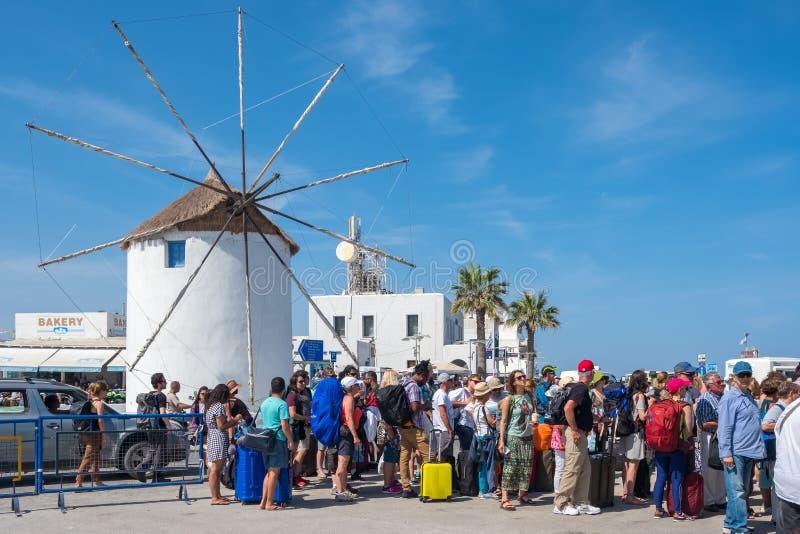 Oidentifierade turister som väntar i linje till färjan med en traditionell cycladic väderkvarn på bakgrund på den Paros ön, royaltyfri fotografi