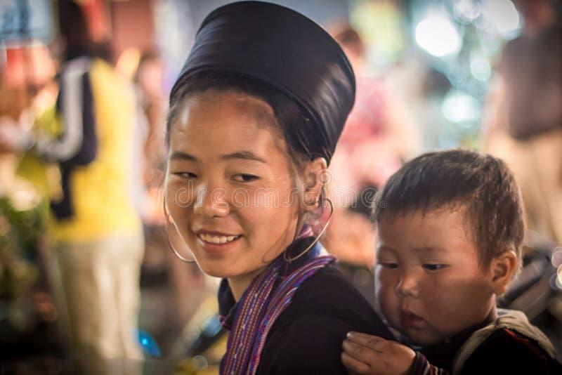 Oidentifierat bära för den Hmong flickan behandla som ett barn i Sapa, Lao Cai, Vietnam arkivbilder